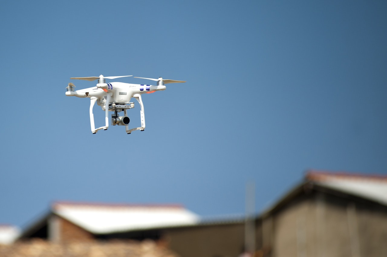 a white drone flying above houses